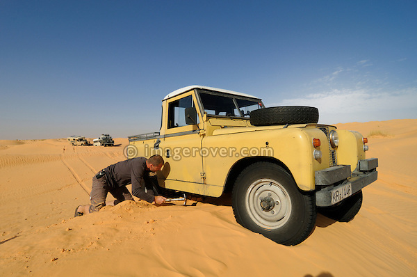 Africa, Tunisia, nr. Tembaine. Desert traveller Frank got stuck with his 1964 Land Rover Series 2a Truck Cab while traversing sand dunes close to Tembaine on the eastern edge of the Grand Erg Oriental. --- No releases available, but releases may not be needed for certain uses. Automotive trademarks are the property of the trademark holder, authorization may be needed for some uses.