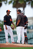 GCL Orioles pitching coach Wilson Alvarez talks with pitcher Miguel Bautista (54) and catcher Stuart Levy during the second game of a doubleheader against the GCL Rays on August 1, 2015 at the Ed Smith Stadium in Sarasota, Florida.  GCL Orioles defeated the GCL Rays 11-4.  (Mike Janes/Four Seam Images)