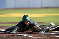 Michigan State outfielder Joe Stewart (5) slides headfirst at home and rips up the turf against the Michigan Wolverines on March 21, 2021 in NCAA baseball action at Ray Fisher Stadium in Ann Arbor, Michigan. Michigan scored 8 runs in the bottom of the ninth inning to defeat the Spartans 8-7. (Andrew Woolley/Four Seam Images)