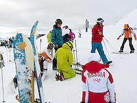 """Switzerland. Canton Valais. Russian snowboarder and skiiers in Verbier at  """" La Chaux"""" ( 2260 meters ). Verbier is a village located in the municipality of Bagnes in the Val de Bagnes. Verbier is one of the largest holiday resort and ski areas in the Swiss Alps. Russian tourists. Woman standing on her knees. 3.01.2012 © 2012 Didier Ruef"""