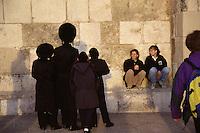 ISRAELE, Gerusalemme. Un gruppetto di ebrei ultraortodossi al muro del pianto osservati da alcuni turisti.