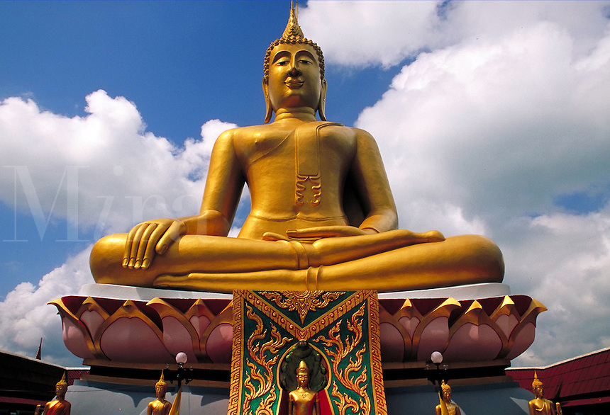 Looking up at large golden Buddha statue with blue sky and big white cumulus clouds. Buddha. Ko Samui, Thailand.