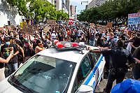 NEW YORK, NEW YORK - June 19: Protesters roll a police car that will not let them cross on June 19, 2020. People gathered in New York at different locations to celebrate June 15, which remembers the day in 1865. When Union soldiers freed slaves, all movements are celebrated in the context of protests against the murder of George Floyd and other African Americans by the police in the USA. USA (Photo by Pablo Monsalve / VIEWpress via Getty Images)