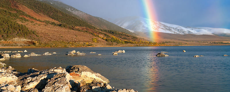 Rainbow with reflection and snow in mountains at Mono Lake. California.