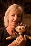 Woman poses with hand made doll she made.  Feelings of love, calm, accomplishment, gratitude.