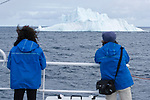 Two expedition members watch an iceberg pass by near Baffin Island, Canada. The women are members of the Cape Farewell Youth Expedition that was organized by the British Council of Canada.