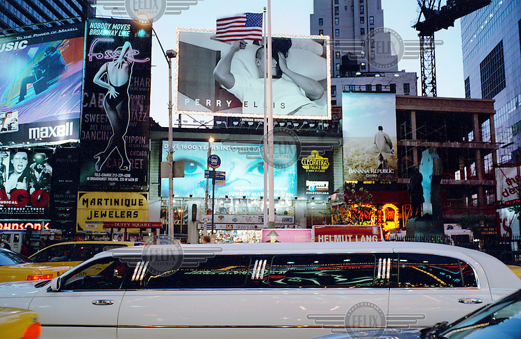 A stretch limo passes advertising billboards on a busy Manhattan street.