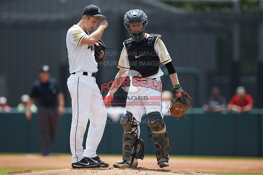Army Black Knights catcher Jon Rosoff (7) has a meeting on the mound with starting pitcher Matt Ball (34) during the game against the North Carolina State Wolfpack at Doak Field at Dail Park on June 3, 2018 in Raleigh, North Carolina. The Wolfpack defeated the Black Knights 11-1. (Brian Westerholt/Four Seam Images)