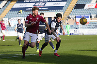 13th March 2021; Dens Park, Dundee, Scotland; Scottish Championship Football, Dundee FC versus Arbroath; Jason Thomson of Arbroath and Declan McDaid of Dundee race for the ball