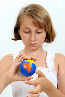 Girl (10) playing with small Earth Globe in hands (Licence this image exclusively with Getty: http://www.gettyimages.com/detail/102966071 )