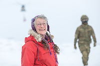 Volunteer Kaisa-Wenche Vivisdatter watching British soldiers on a helicopter mission to transport firewood to a remote Norwegian cabin. The newly built Vouma cabin in Dividalen National Park is part of the Norwegian Trekking Association network. As a goodwill gesture and part of their Arctic training the Royal Navy use helicopters to fly firewood to the remote location. <br /> <br /> <br /> In 2019 the Arctic exercise Clockwork passed 50 years of training in Norway, and now has a permanent base within the Norwegian Air Force base at Bardufoss. <br /> <br /> 845 Naval Air Squadron is a squadron of the Royal Navy's Fleet Air Arm. Part of the Commando Helicopter Force, it is a specialist amphibious unit operating the Leonardo Commando Merlin Mk3 helicopter and provides troop transport and load lifting support to 3 Commando Brigade Royal Marines.<br /> <br /> ©Fredrik Naumann/Felix Features
