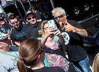 Apr 12, 2015; Las Vegas, NV, USA; Celebrity chef Guy Fiere poses for photos with fans in the pit area of NHRA top fuel driver Shawn Langdon during the Summitracing.com Nationals at The Strip at Las Vegas Motor Speedway. Mandatory Credit: Mark J. Rebilas-