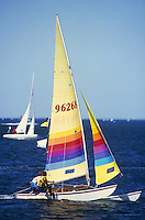 Two sailors in a small sailboat with coloured sail