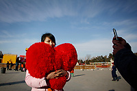 CHINA. A woman holding a heart during Chinese New Year in Ditan Park in Beijing.  Chinese New Year, or Spring Festival, is the most important festival and holiday in the Chinese calendar In mainland China, many people use this holiday to visit family and friends and also visit local temples to offer prayers to their ancestors. The roots of Chinese New Year lie in combined influences from Buddhism, Taoism, Confucianism, and folk religions.  2008