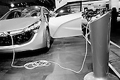Detroit, Michigan<br /> USA<br /> January 14, 2010<br /> <br /> Industry preview day at the North American International Auto Show at the Cobo center in Detroit. Auto manufactures are free to check out the produces of other manufactures - in detail. <br /> <br /> Electric car plugged in.<br /> <br /> Automotive professionals representing nearly 1,000 companies, including America's big three; Ford, General Motors and Chrysler, share insights and make connections on this day of the show. A networking opportunity that brings together the latest automotive products and services with the key minds behind them.