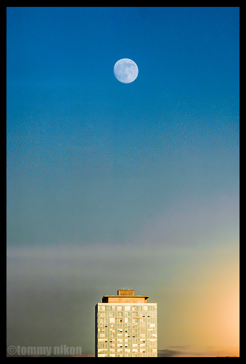 """Full moon dotting the """"I"""" over a building"""