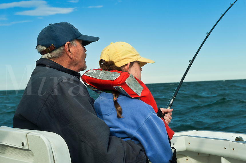 Senior man teacing grand daughter to fish.