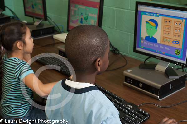 Elementary school male and female students using computers in science lab