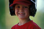 portrait of young boy playing baseball wearing batting helmet