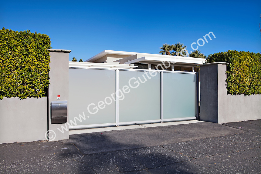 Motorized frosted glass sliding gate leads to motorcourt