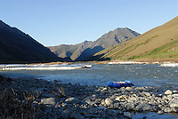 A raft gives scale to the water, ice and mountains along the Kongakut River, in Alaska's Arctic National Wildlife Refuge.