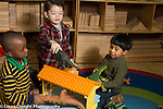 Education preschool 3-4 year olds group of three boys playing with doll house and toy dinosaurs