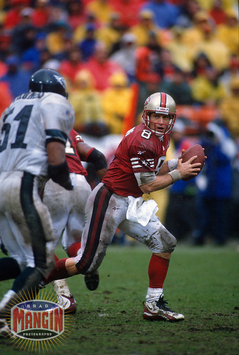 SAN FRANCISCO, CA:  Quarterback Steve Young of the San Francisco 49ers drops back to pass in the rain during the NFC playoff game against the Philadelphia Eagles at Candlestick Park in San Francisco, California on December 29, 1996. (Photo by Brad Mangin)