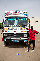 """Senegal, Touba.  Inter-city transport bus.  """"Alhamdoulilahi"""" is Arabic for """"Praise be to God."""" an expression of thanksgiving.  The young man is the fare-collector on the bus."""