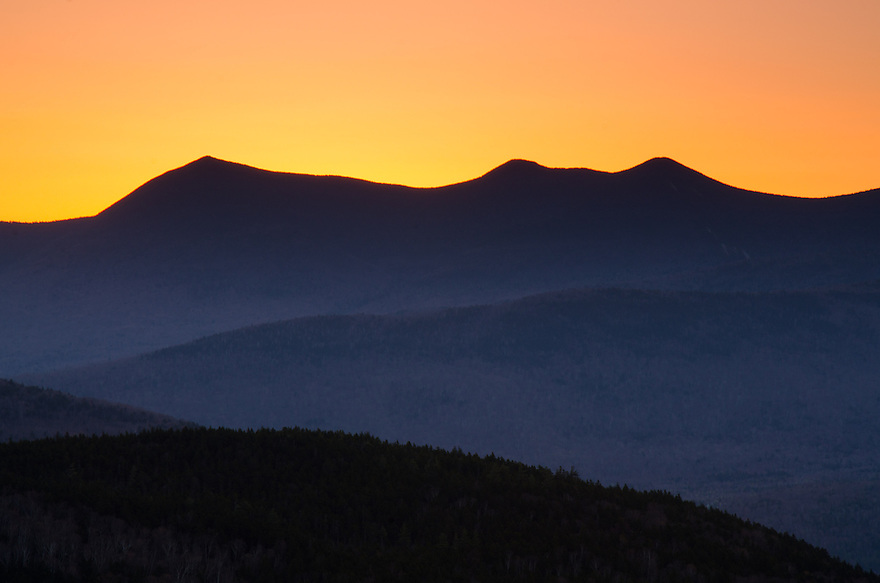 The sky turns to gold moments before the sun rises over Mt Tripyramid in New Hampshire's White Mountains.