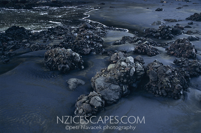 Black volcanic sand and volcanic rocks on the Whatipu Beach on the west coast of Auckland.