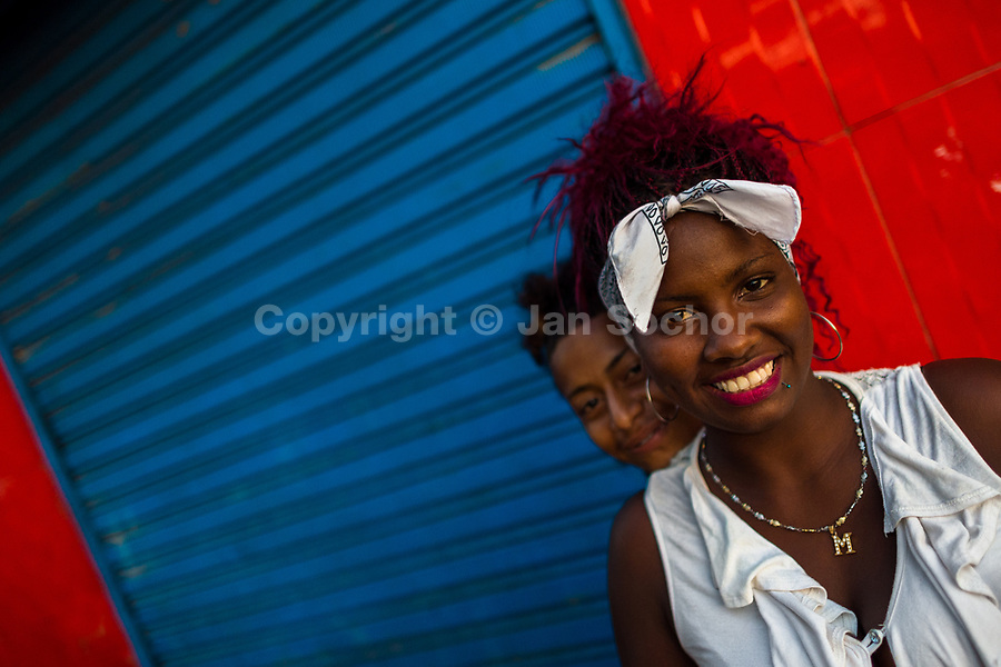 Afro-Colombian market vendors pose for a picture, showing their relationship, in the market of Bazurto in Cartagena, Colombia, 4 December 2018. Far from the touristy places in the walled city, a colorful, vibrant labyrinth of Cartagena's biggest open-air market sprawls to the Caribbean seashore. Here, in the dark and narrow alleys, full of scrappy stalls selling fruit, vegetables and herbs, meat and raw fish, with smelly garbage on the floor and loud reggaeton music in the air, the African roots of Colombia are manifested.