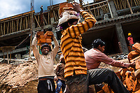 Bangladeshi migrant workers carrying bricks on their heads on a construction sites in Thimphu.
