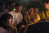 Japanese and foreign nationals crowd around a television set outside a storefront in Yokohama, Japan to watch the finals of the FIFA 2002 World Cup between Brazil and Germany. Brazil defeated Germany 2-0.