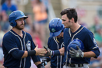 Sam Hilliard (right) slaps hands with teammate Brian Mundell (left) after hitting a home run against the Kannapolis Intimidators at Intimidators Stadium on May 28, 2016 in Kannapolis, North Carolina.  The Intimidators defeated the Tourists 5-4 in 10 innings.  (Brian Westerholt/Four Seam Images)