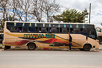 Tanzania.  Mto wa Mbu. Vendor Offering Goods to a Passenger on a Long-distance Bus.