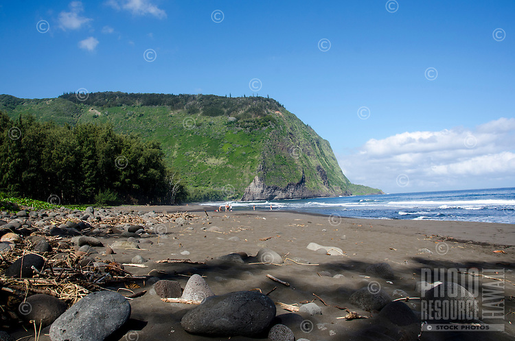 Visitors enjoy the black sand beach at Waipi'o Valley, Hamakua District, Island of Hawai'i.