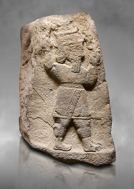 Aslantepe Hittite relief sculpted orthostat stone panel Limestone, Aslantepe, Malatya, 1200-700 BC. Anatolian Civilizations Museum, Ankara, Turkey.<br /> <br /> A short-dressed and winged demon (mixed creature), and on the third face is the Storm God. The Storm God holds a triple lightning bundle in his left hand and a hammer in his right hand. His both arms are in an upright position. <br /> <br /> Against a grey art background.