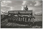 Scan of vintage print. Farmer with grain drill and bag of corn seed. Negative file #74-128-C. 1974. 1 of 1