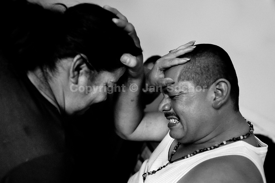Colombian believers, pressing on each other's foreheads, attempt to evict supposed demons during the exorcism ritual performed at a house church in Bogota, Colombia, 28 January 2013. Hundreds of Christian belivers, joined in nameless groups, gather every week in unmarked home churches dispersed in the city outskirts, to carry out prayers of liberation and exorcism. Community members and their religious activities are usually conducted by a charismatic pastor or preacher. Using either non-contactive methods (reading religous formulas from bible, displaying Christian symbols and icons) or rough body-pressure-points techniques and forced burping, a leading pastor commands the supposed evil spirit, which is generally believed to come from witchcraft, to depart a person's mind and body. The demon's expulsion often consists of multiple rites and may last for several months.