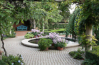 Circular pond and stepping stone patio by arbor with bench at Chicago Botanic Garden