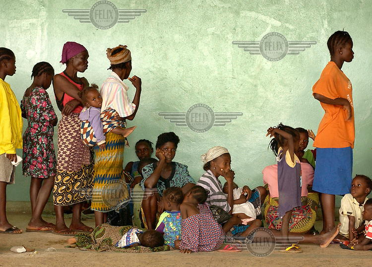 Women wait in the basement of the Samuel K Doe stadium, where about 15,000 internally-displaced people (IDPs) had taken refuge, for their children to be weighed and registered by staff from Medecins sans Frontieres (MSF). .The ongoing conflict in Libera intensified in March 2003 when rebels opposed to the government of Charles Taylor gained territory across much of the country, advancing on the capital city Monrovia. In August 2003 Taylor agreed to hand over power to an interim government and went into exile in Nigeria, which led to the signing of a peace agreement. Taylor was indicted for war crimes by a UN court in Sierra Leone, accused of fuelling conflict across several West African countries.