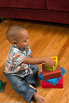 21 month old toddler boy building playing with stacking colorful cardboard blocks