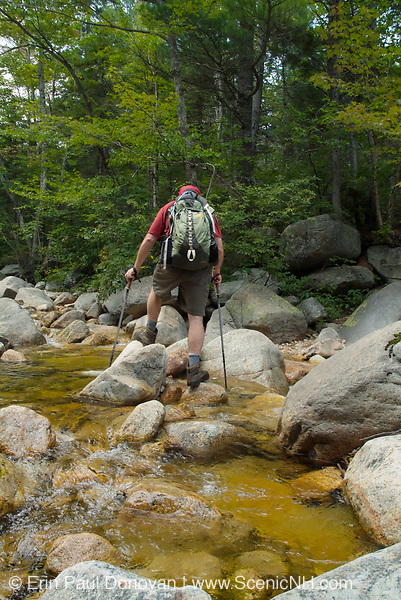 A hiker crossing the Swift River along the Sawyer River Trail in the White Mountains, New Hampshire during the summer months.