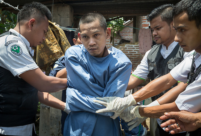 """5 April 2017, Surabaya,East Java,Indonesia: Febrianto, a 24 year old mental illness sufferer is placed in a strait jacket after his release from the chains he has been shackled to a stake for the past two years in a goat shed next to his family in Pehwetan village, East Java. Indonesian Social Affairs Dept. workers cut the bonds and washed his emaciated body and apply first aid before putting him in an ambulance and taking him to a facility in Malang for treatment. Febrianto is a patient in a program called """"E- Shackling"""" which aims to free people suffering from mental illness, from the shackles that family often place them in to control them in the wake of a lack of treatment options and which will treat them and enter them in a data base allowing them to be traced before releasing them back to their families. Some people stay chained to a stake or in rooms for years by their families and not all families are willing to take their sick family members back. Picture by Graham Crouch/The Australian"""