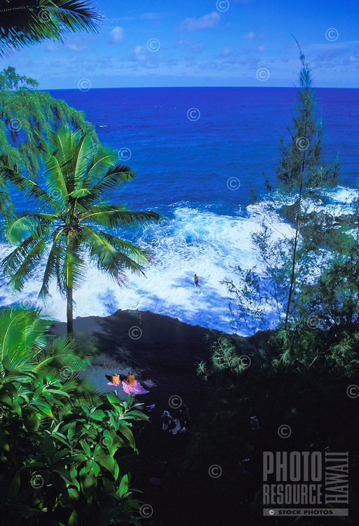 People relax on Kahena Black Sand Beach.  A very secluded beach in the Puna area of the big isle, south of Hilo.  It  is common to see nudists at this beach.