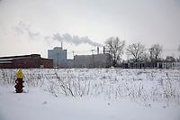 Detroit: paesaggio urbano. Distesa di neve con all'orizzonte palazzi con comignoli fumanti.