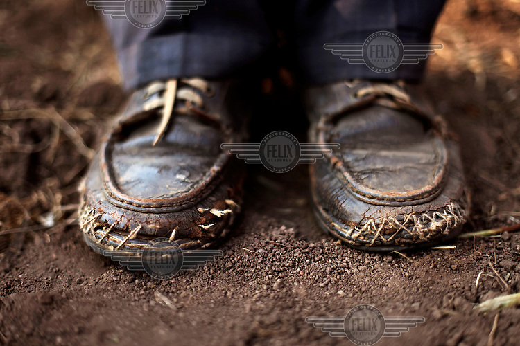 """The much repaired shoes of Eugene Nzeyimana (42) a volunteer distributor of medication in his area. Although he works for free he says: """"it would be nice to be given a small reward or motivation for our work because we have to leave our fields. Somtheing like a bar of soap or a new pair of shoes."""" In every village of Bururi, Rutana, Cibitoke and Bubanza Provinces a small team of local volunteers make up a distribution team for the Drug Administration Campaign for Neglected Tropical Diseases. They check off members of the population, measure them to decide what drugs to give and the dose, administer them and keep a tally of numbers in order to help the health authorities reach all parts of the rural population. Four provinces in Burundi are severly affected by Neglected Tropical Diseases such as Onchocerchiasis (River Blindness), Schistosomiasis (bilharzia) and STH's (Soil Transmitted Helminths). Each year thousands of local volunteers give up their work for up to 2 weeks to distribute of medicines in their villages for The Distribution Campaign for Neglected Tropical Diseases run by the Ministry of Health. Onchocerchiasis is the world's second-leading infectious cause of blindness and causes serious itching and inflammation of the skin. It is spread by flies that breed by water. Schistomiasis is a form of worms, a chronic illness that can damage organs and cognitive delevopment in children and is spread by playing or washing in infected waters. STH's are intestinal worms which produce a large range of symptoms including diarrhoea, pains, and a general malaise that may affect working and learning capacities and impair physical growth. /Felix Features"""