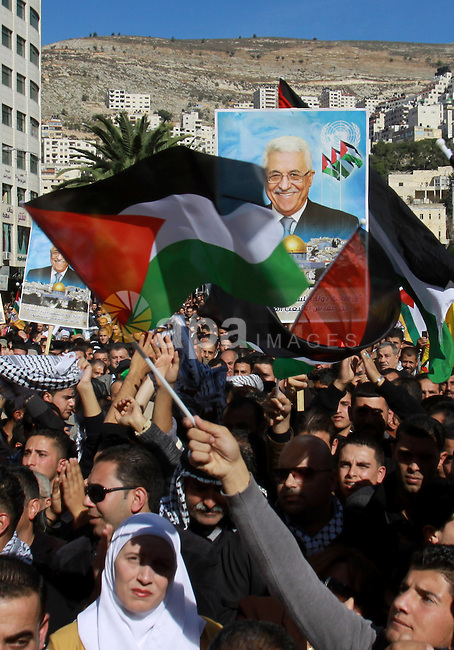 Palestinians hold up portraits of Palestinian President Mahmoud Abbas during a rally supporting the Palestinian UN bid for observer state status, in the West Bank city of Nablus, 29 November 2012. Abbas is to press the United Nations to recognise Palestine as an 'observing state'. The move comes on International Day of Solidarity with the Palestinian People. Photo by Nedal Eshtayah