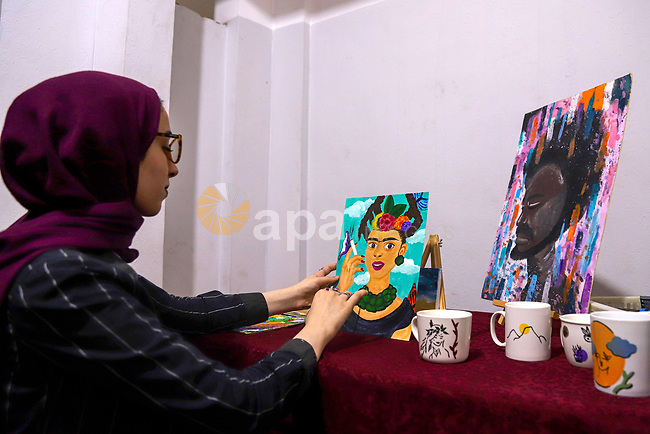 Palestinian artist, Farah Al-Ajl, 20, paints a painting on a papers at her home, in Gaza city on May 4, 2021. Al-Ajl, is studying business administration, where she works in this profession to help herself to complete her study. Youth (19- 29 years) are the most group suffering from unemployment. Thus, the unemployment rate among youth reached about 39%; 24% in the West Bank and 67% in Gaza Strip. Moreover, the youth graduates of those who hold a scientific qualification of an intermediate diploma or higher are the most group suffering from unemployment, as this rate reached about 54%; (36% in the West Bank and 79% in Gaza Strip). Photo by Mohammed Salem
