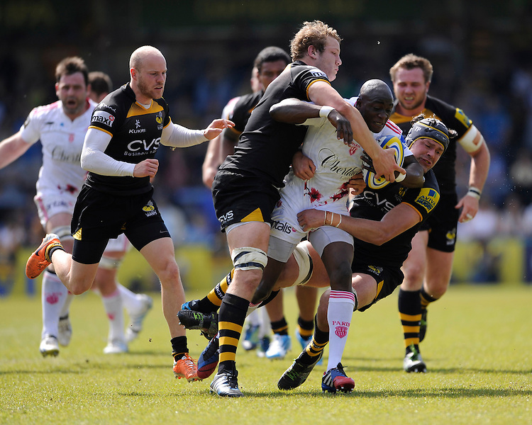 Djibril Camara of Stade Francais is tackled by Joe Launchbury and Tom Palmer of London Wasps during the first leg of the European Rugby Champions Cup play-off match between London Wasps and Stade Francais at Adams Park on Sunday 18th May 2014 (Photo by Rob Munro)